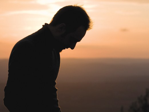 Stock image of a man looking down with a sunset in the background. © iStockphoto.com
