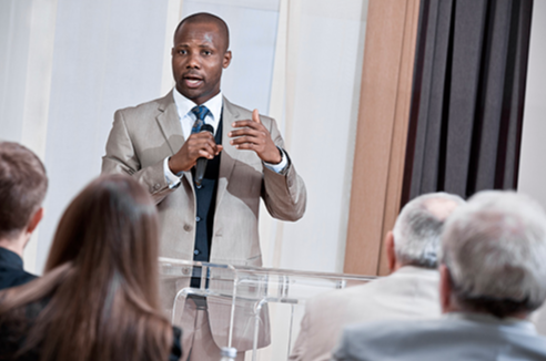 Stock image of a speaker addressing a group of people.
