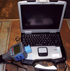 Radioisotope identification device (RIID) connected to a laptop. This unit can identify various radioactive isotopes. The spectra files can be downloaded onto a laptop computer that has the proper transfer software installed using either a serial cable or a USB cable.