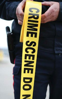 Officer Unrolling Crime Scene Tape