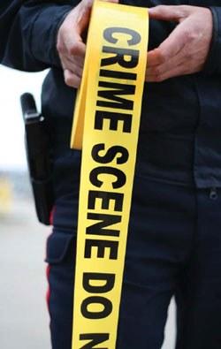 Officer Unrolling Crime Scene Tape