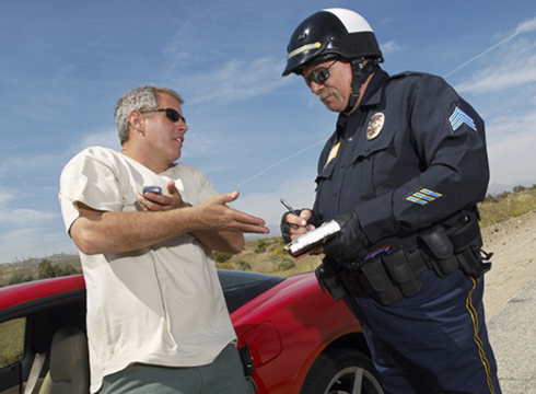 Stock image of a police officer writing a ticket to a motorist with a sports car.