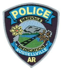 The patch of the Russellville, Arkansas, Police Department features several symbols significant to the area. These include the arrowhead, atom, landscape, railroad line, ship's wheel, and cog.