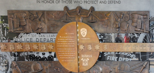 The San Leandro Public Safety Memorial in California depicts police offers, firefighters, and their respective equipment. The back face of the memorial is etched black granite illustrating historic photographs.