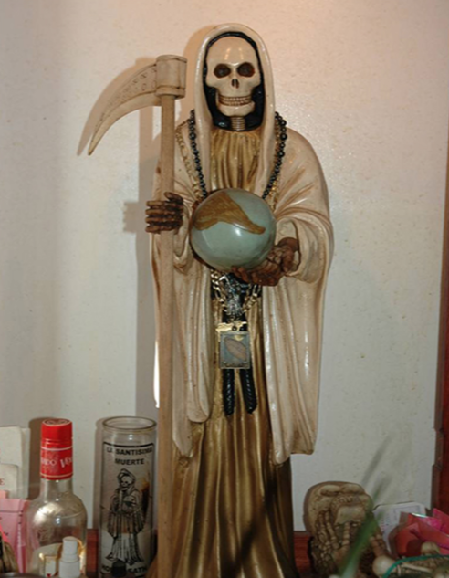 Depiction of a Santa Muerte statue wearing a white cape, symbolizing personal protection. Photo provided by U.S. law enforcement.