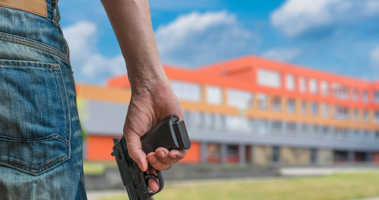 A stock photo of a youth male standing in front of a school holding a gun in his hand.