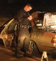 A police officer searches a car.