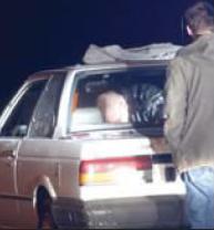 Suspect Stands Behind Vehicle Under Inspection