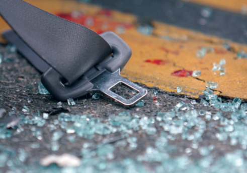Stock image of a seatbelt surrounded by broken glass and blood.