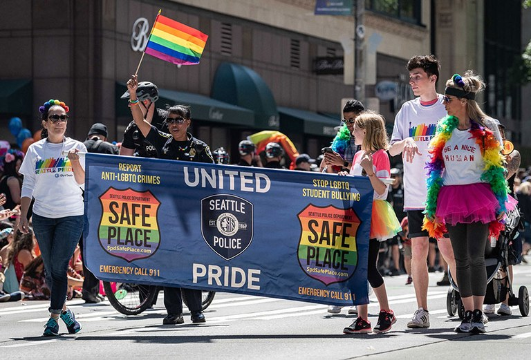 An image of officers and the community holding a Safe Place initiative banner in a parade.