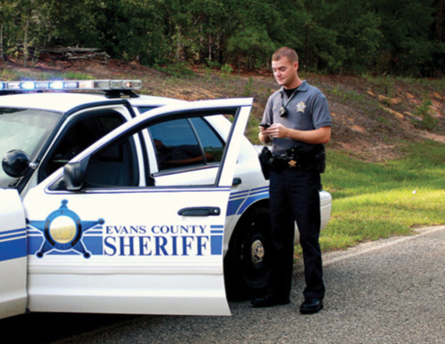 A sheriff examines his smartphone while near his vehicle.