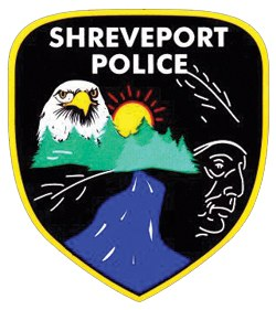 Various milestones in the history of Shreveport, Louisiana, are depicted on the patch of its police department. Flowing prominently at the bottom is the Red River, along which Shreveport was founded in 1833. The trees featured in the center represent the logging industry, and the American eagle symbolizes integrity and freedom. To the right is a profile of the Caddo Indian, who once occupied the local territory.