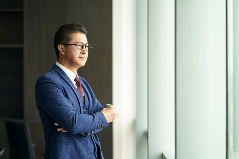 A stock image of a business man looking out the window thinking.
