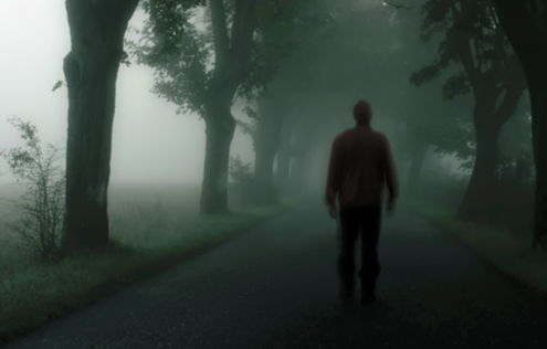 Stock image of a man walking along a misty, tree-lined road. © shutterstock.com.