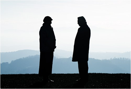 Stock image of two men in silhouette talking outside with mountains in the background.