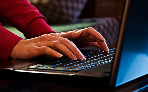 Stock image of a woman typing on a laptop keyboard.