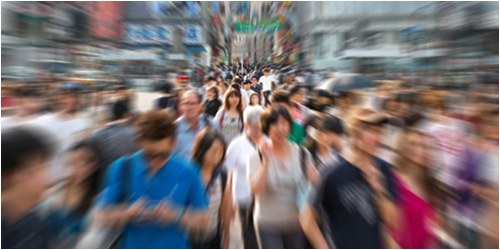 Stock image of a blurred crowd of people in a city setting.