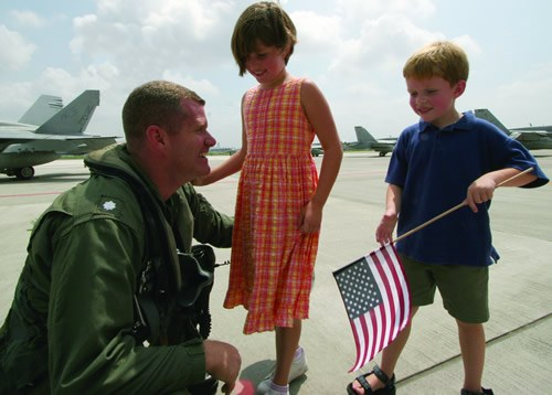 Solidier on Tarmac with Two Children