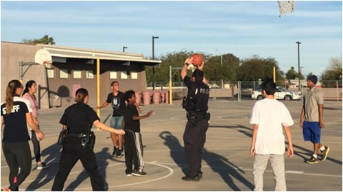 Scottsdale, Arizona Police Department officers playing basketball with kids as part of the Partnering Law Enforcement and Youth (P.L.A.Y.) outreach program.