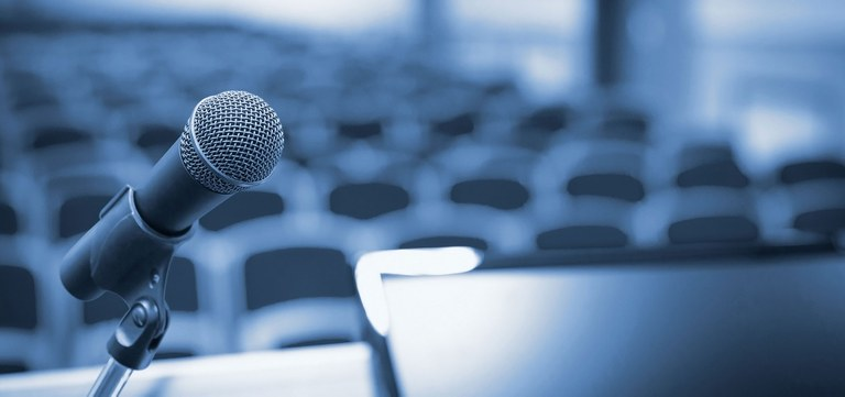 A stock image of a microphone and speaker podium.
