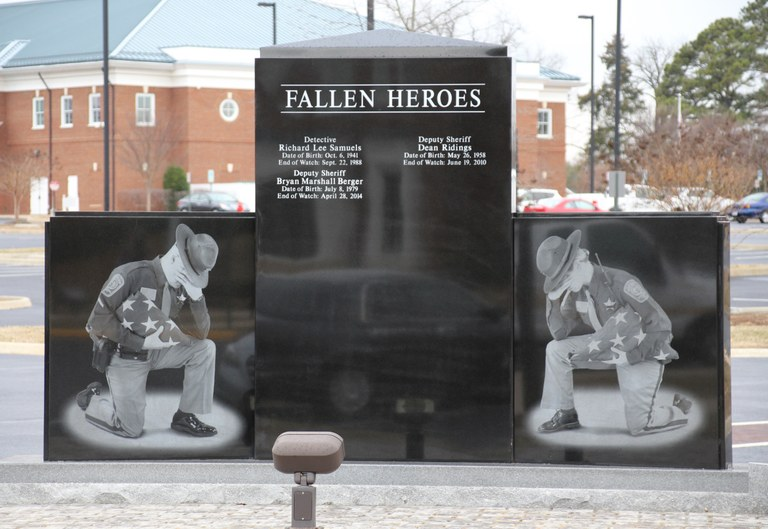 Photo of the Spotsylvania County Sheriff's Office Law Enforcement Memorial. The photo depicts the side of the memorial which includes images of a female and male officer kneeling while holding a folded American flag and the engraved names of those who have died in the line of duty between the two officers.
