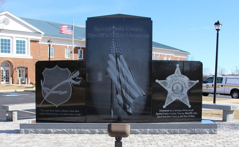 Photo of the front of the Spotsylvania County Sheriff's Office Law Enforcement Memorial which includes the symbolic blue badge and rose, the American flag, and the badge of the Spotsylvania County Sheriff's Office.