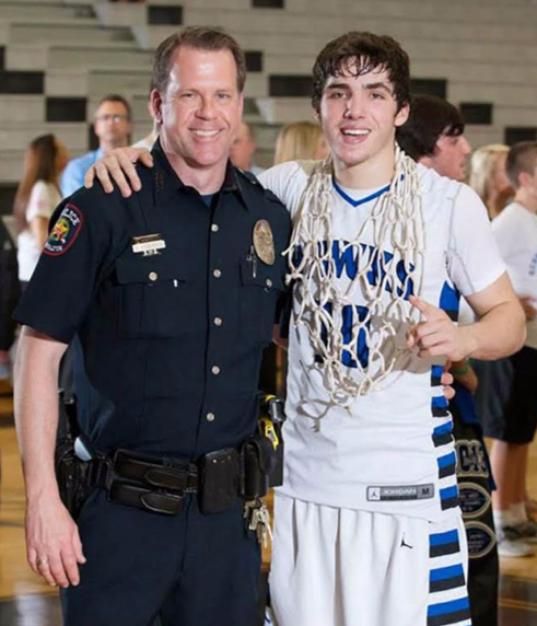 A school resource officer stands alongside a victorious high school basketball player.