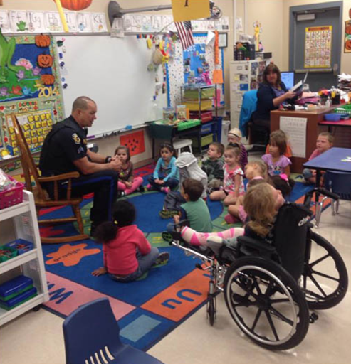 A school resource officer is shown interacting with grade school students in their classroom.