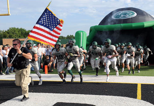 A school resource officer is shown leading high school football players onto the field of play.