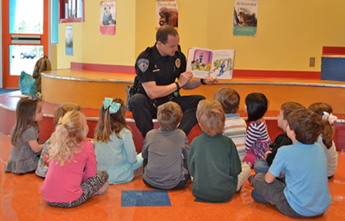 A School Resource Officer is depicted reading to the children he protects.