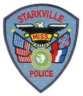 The Starkville, Mississippi, Police Department's patch displays symbols of both United States and state pride. The top image, a bald eagle, recognizes patriotism and courage. The magnolia, Mississippi's state flower, is depicted in full boom, encircled by double yellow lines that represent the department's personnel. Finally, the United States and Mississippi flags surround the magnolia to pay homage to the nation and state the department serves.