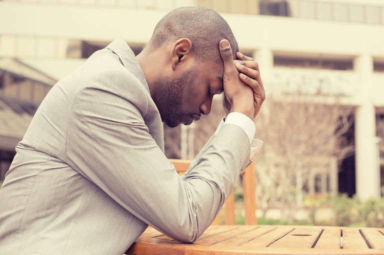 A stock image of a business man sitting outside of his workplace with his hands on his forehead.