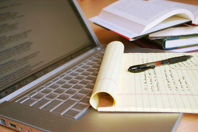 A stock image of a laptop, textbooks, and a notepad.