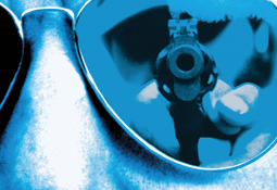 Stock image of a man with a gun is reflected in the glasses of his victim.