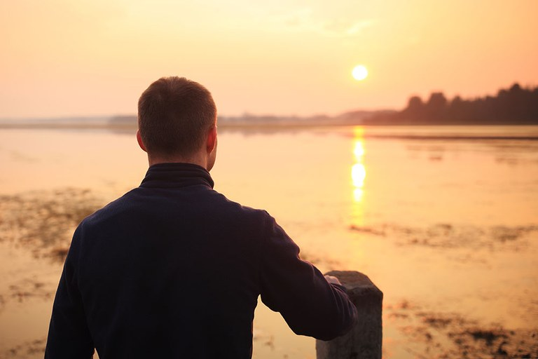 A stock image of a middle-aged man looking into the sunset.