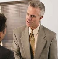 Stock image of a man in a suit talking to another man.