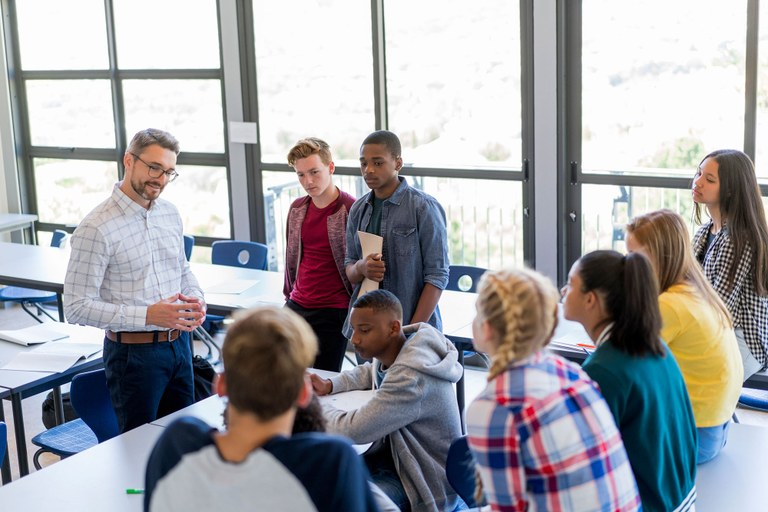 A stock image of a teacher have a discussion with teen students.