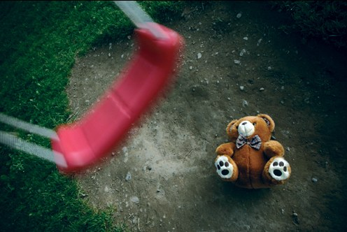 Stock image of a teddy bear on the ground under an empty swing in a park. © Thinkstock.com
