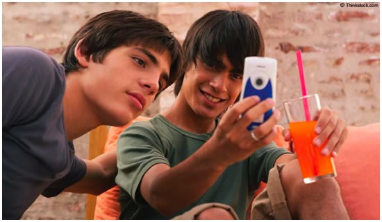 Teen Boys Looking at Cell Phone (Stock Image)