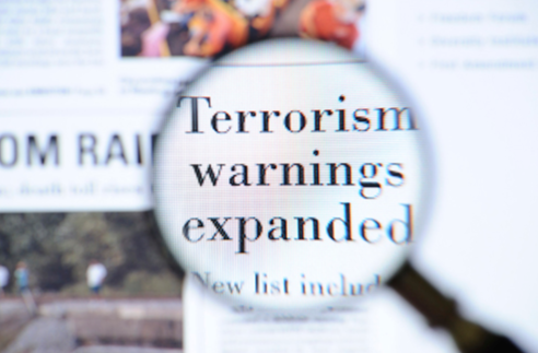 Stock image of a magnifying glass showing a closeup of a terrorism headline.