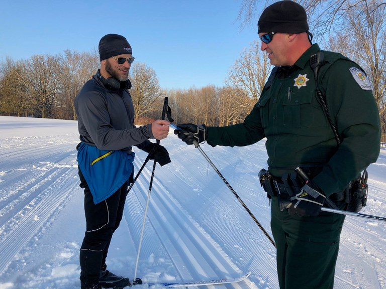 A Three Rivers Park police officer providing assistance to a skier.