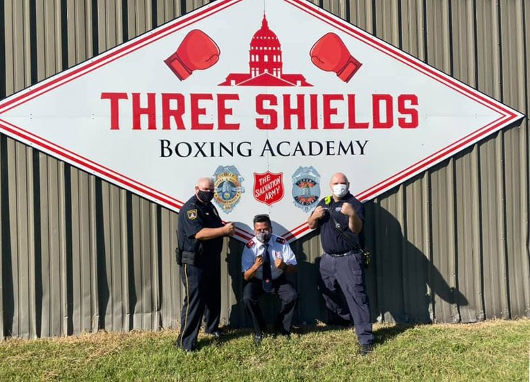 A photo of three officers in front of the Three Shields Boxing Academy building and logo.
