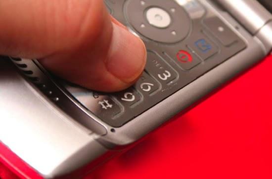 Thumb on Cell Phone Keypad (Stock Image)