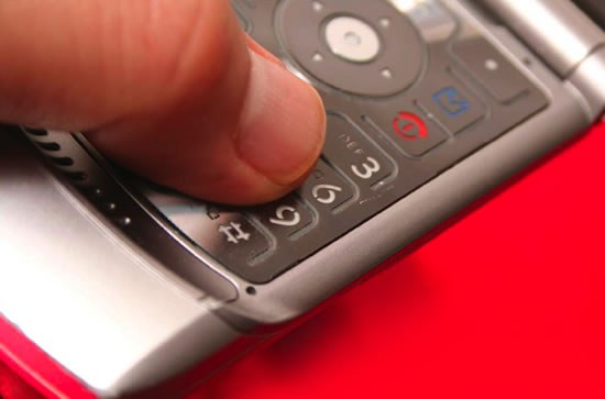 Thumb on Cell Phone Keypad (Stock Image)