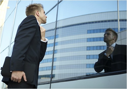 Man Straightening Tie in Building Glass (Stock Image)