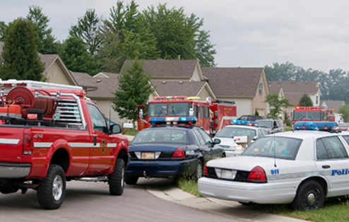 Police cars and fire trucks arrive in a neighborhood to respond to an incident.