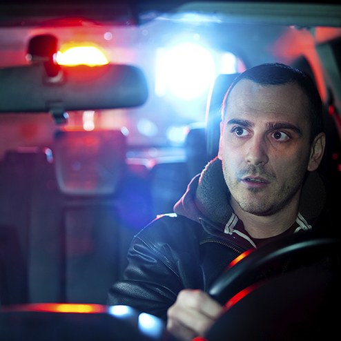 Stock image of a man looking in his rearview mirror at a car right behind him.