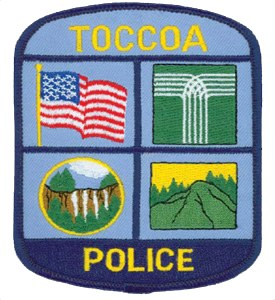 "Sectioned into four unique squares, the patch of the Toccoa, Georgia, Police Department patch represents the city, state, and nation that the agency protects. The green and white ""T"" graphic displays the city logo; its shape mimics the picturesque Toccoa Falls illustrated in the bottom left section of the patch. The bottom right depicts another Georgian geographical wonder, the Currahee Mountain, named for the Cherokee word for ""stand alone."""