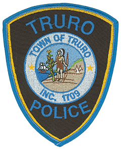 The town of Truro, Massachusetts, was incorporated in 1709 after being settled nine years earlier by British colonists from the nearby town of Eastham. The area was visited in 1620 by the pilgrims from Plymouth colony on their way to establishing a permanent settlement in the New World. This scene is depicted on the Truro town seal, which is featured on the service patch of the Truro Police Department. In the center, a Wampanoag American Indian chief is shown next to a stalk of corn, the food source which ensured the pilgrims' survival during their first years. A Wampanoag community is represented by two teepees on the right, while the pilgrims' ship, the Mayflower, is shown on the left at sea.