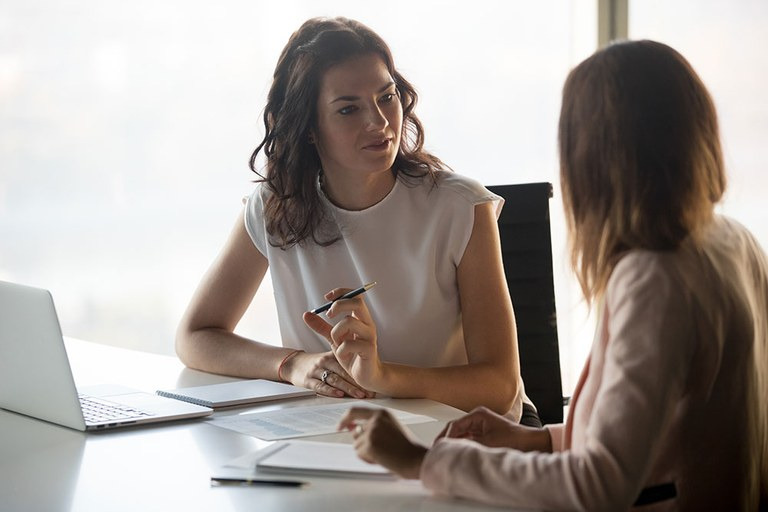 A stock image of two female business professionals conversing.